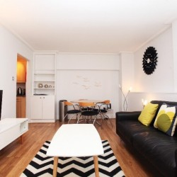 living room with TV, white coffee table, brown leather sofa with 3 cushions, dining table with 4 chairs, book shelf, clock on wall