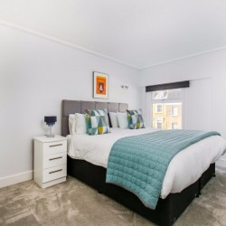 bedroom with double bed, blue bed spread, side table with lamp, artwork on wall