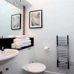 bathroom with sink, toilet rolls, towels, heater and toilet