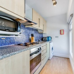 kitchen with blue wall tiles, microwave, oven, 4 plated hob, sink. toaster, washer dryer