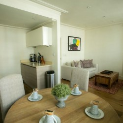 kitchen and living room with sofa, dining table, chair, lamp and artwork