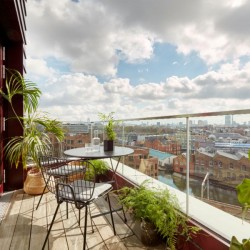 balcony with view of London, table, 2 chairs, several plants