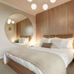 bedroom with double bed, large round mirror, side table