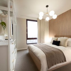 bedroom with king size bed, ceiling lamp, storage with drawers and plant