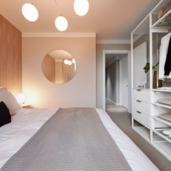 king size bed, round mirror, celiling lamp and wardrobe with clothes, shoes, open door to hallway