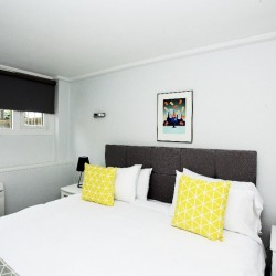 bedroom with double bed, 2 yellow cushions, side table with lamp, artwork on wall