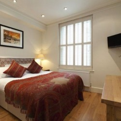 double bed, chest of drawers, tv, side table with lamp