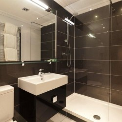 bathroom with shower cubicle, sink, toilet and towel rail