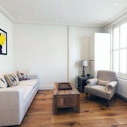living room with sofa, table, chair, lamp and artwork