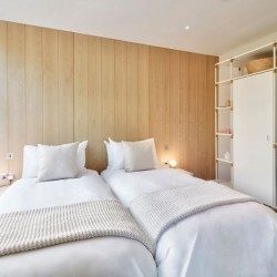 bedroom with twin beds, storage unit with wardrobers, light wooden wall panelling, 2 side tables with lamp